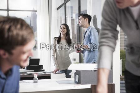 colleagues talking in modern office