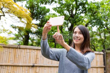 woman using mobile phone to take