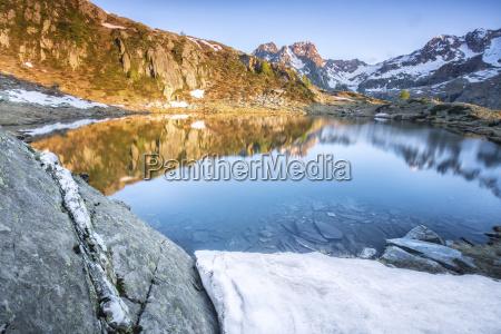 snowy peaks reflected in lake zana