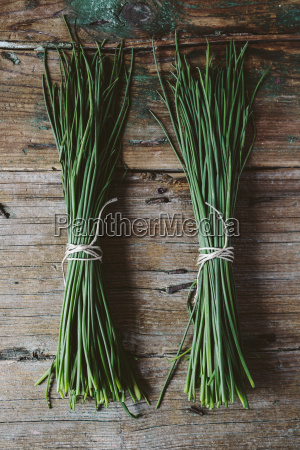 two bunches of chives on wood