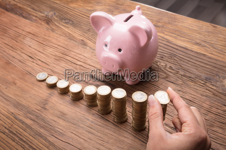 woman placing a coin on stack
