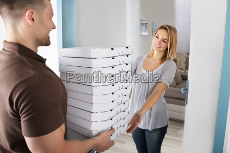 man delivering stack of pizza