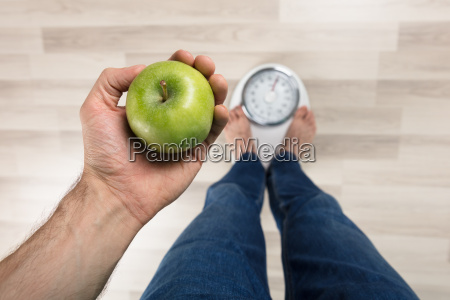 person measuring weight on weighing machine