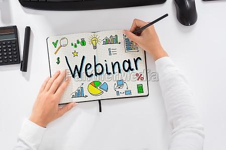 businesswoman drawing webinar chart on notebook