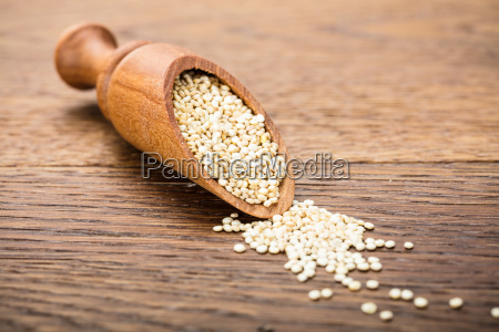 raw white quinoa seeds on wooden