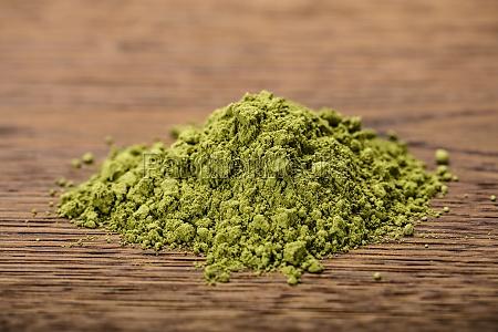 green tea powder on wooden table