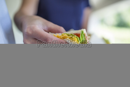 close up of woman taking sandwich