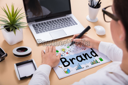 businesswoman drawing brand chart on office