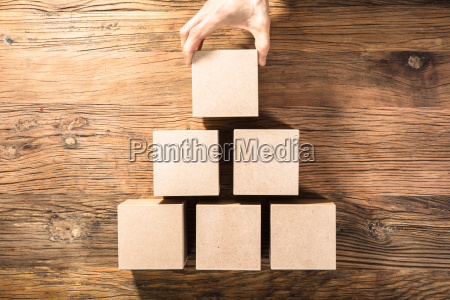 person holding block on wooden table