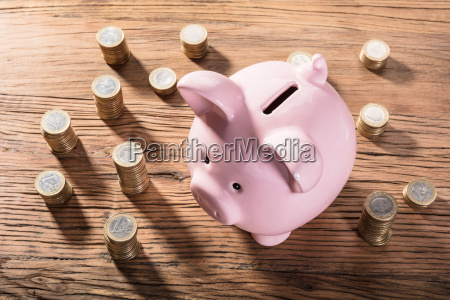 piggybank surrounded with coin stacks