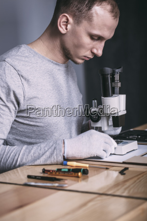 young male technician examining circuit board