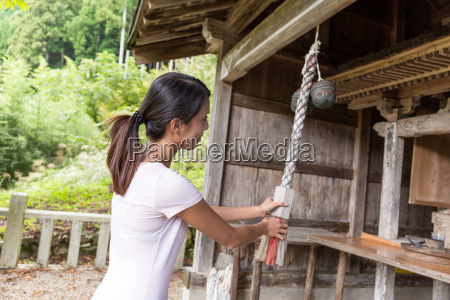 young woman ringing the bell in