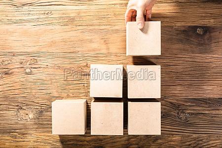 persons hand arranging wooden block