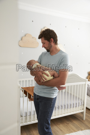 father comforting newborn baby son in