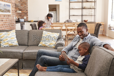 father and son sit on sofa