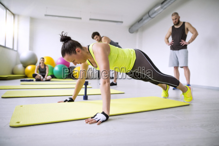 woman exercising in gym watched by