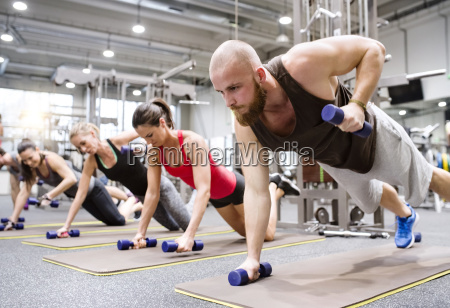 group of athletes exercising with dumbbells