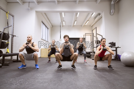 group of athletes exercising with kettlebells