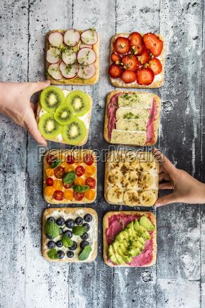 childrens hands taking garnished sandwiches