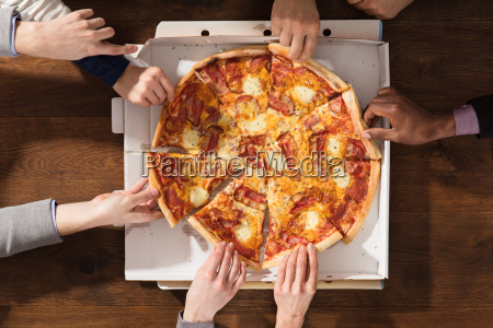 hands taking each slice of pizza