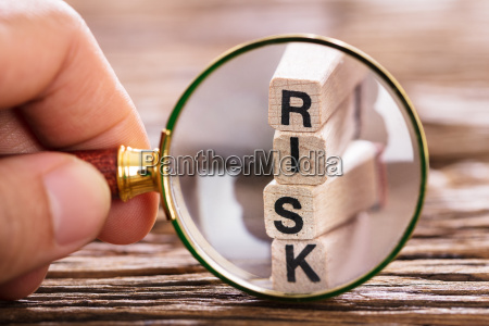 person inspecting risk block with magnifying