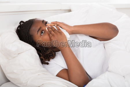 girl blowing her nose with tissue