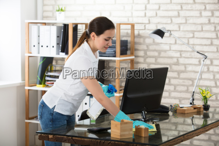 woman cleaning the glass office desk