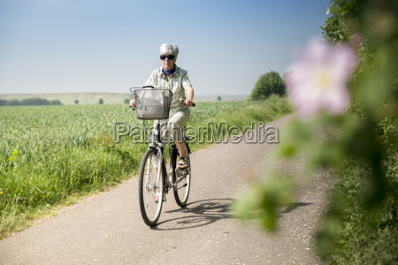 germany senior woman riding bicycle in