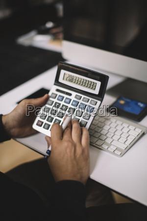 man using calculator at desk partial