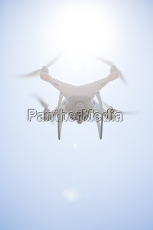 flying drone with camera at backlight