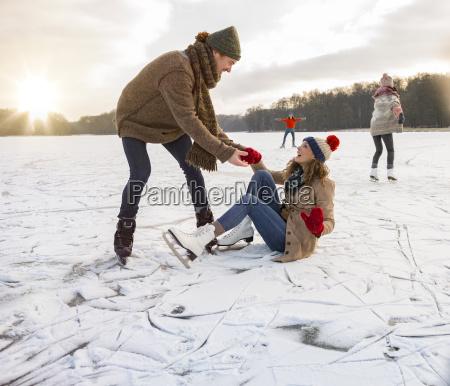 man helping ice skating woman up