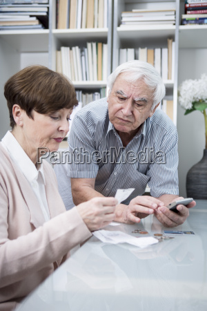 senior couple with bills and calculator
