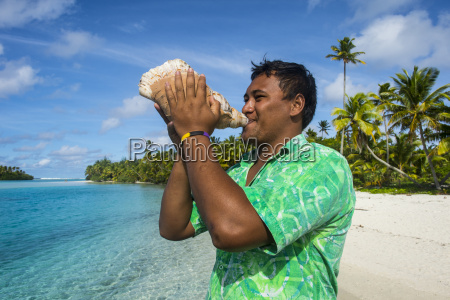 local man blowing a huge conch