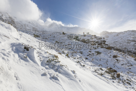 hikers proceed in the snowy valley