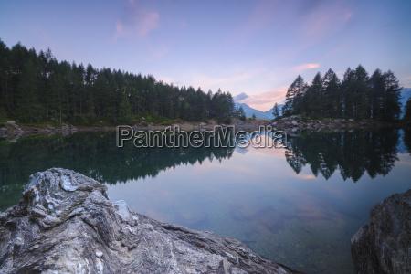 trees reflected in lago azzurro under