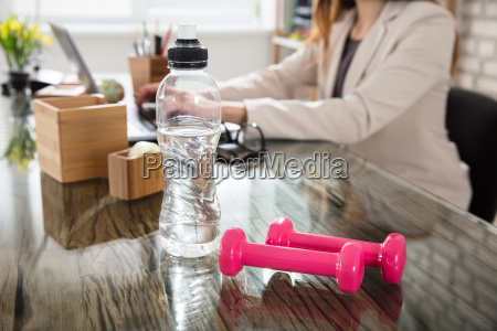 water bottle and fitness dumbbells on