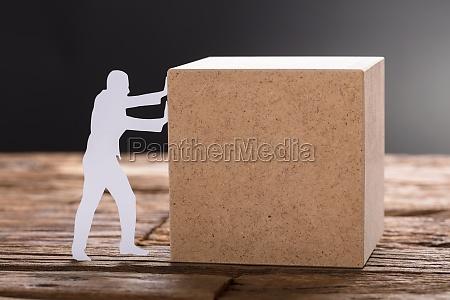 paper man pushing wooden block on