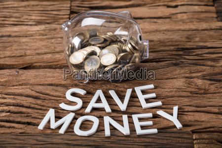 coins in glass piggybank by save