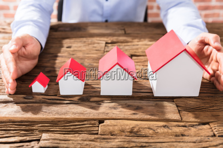 businessman protecting the house models with