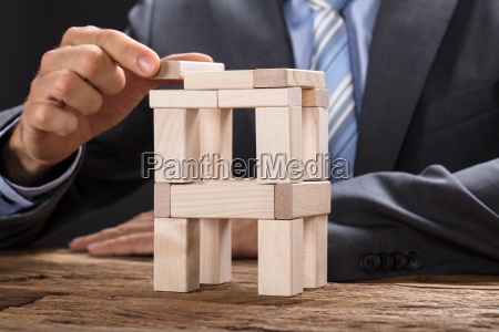businessman building tower with wooden blocks