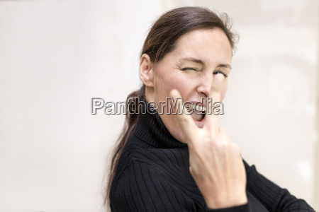 portrait of businesswoman showing victory sign