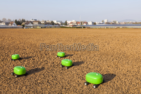 five agricultural robots on a field