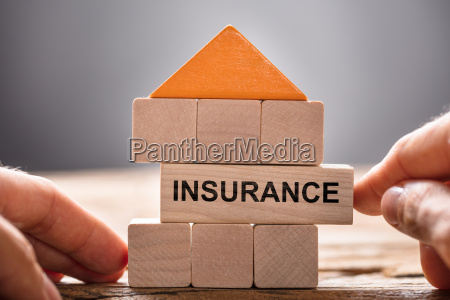 hands building house model with insurance