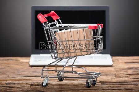 cardboard box in shopping cart with